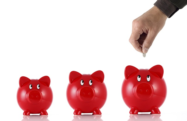 Hand putting coin into three hopeful piggy banks