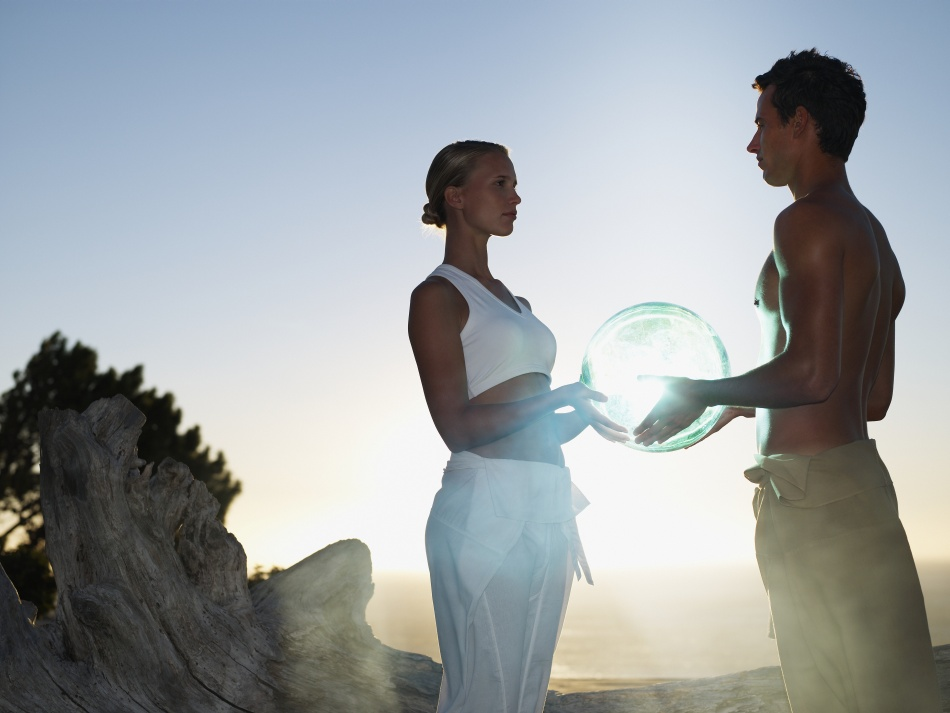 A man and woman holding an orb