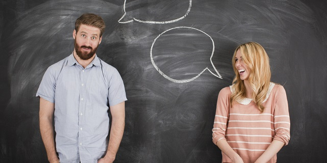 Young couple with speech bubble on blackboard, studio shot